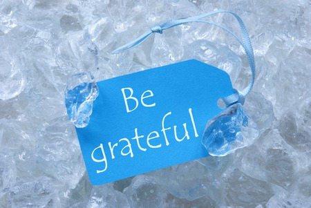 icecubes: Light Blue Label With Blue Ribbon On White Transparent Curshed Ice Cubes As Background. English Text Be Grateful For Cool Greetings.Close Up Or Macro View.