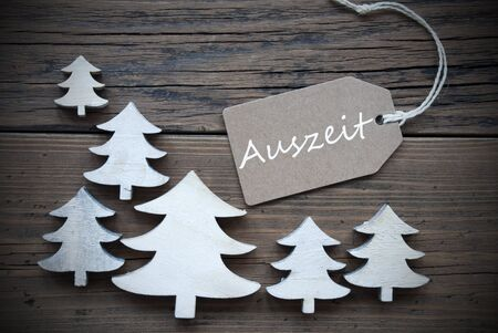 auszeit: Brown Christmas Label With Ribbon On Wooden  Background With White Christmas Trees. Vintage Style. Label With German Text Auszeit Means Downtime For Christmas Or Season Greetings