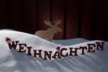 christmas atmosphere: Red Letters Building German Word Weihnachten Means Christmas.Decoration Card For Seasons Greetings. Snow And Snowy Scenery With Moose And Santa Hat. Wooden Background. Christmas Atmosphere