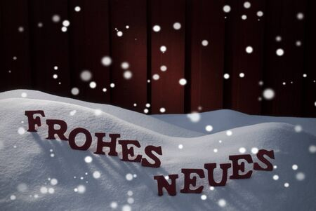 christmas atmosphere: Red Letters Building German Word Frohes Neues Means Happy New Year As Decoration Card For Seasons Greetings. Snow And Snowy Scenery With Snowflakes. Wooden Background. Christmas Atmosphere Stock Photo