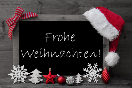 Black And White Blackboard With Red Santa Hat And Christmas Decoration like Snowflake, Tree, Christmas Ball, Fir Cone, Star. German Text Frohe Weihnachten Means Merry Christmas. Wooden Background Stock Photo