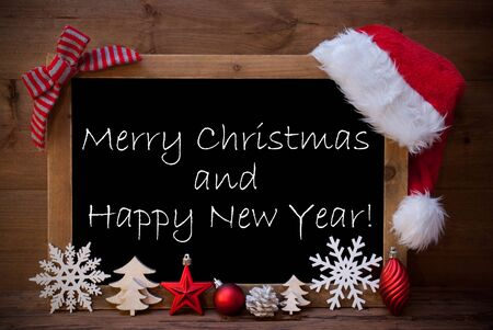 like english: Blackboard With Red Santa Hat And Christmas Decoration like Snowflake, Tree, Christmas Ball, Fir Cone, Star. English Text Merry Christmas And Happy New Year. Brown Wooden Background Stock Photo
