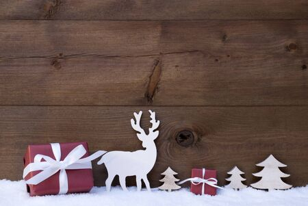free christmas background: Christmas Decoration With Red Gifts Or Presents Moose Or Reindeer And Christmas Trees On Snow. Christmas Card For Seasons Greetings. Copy Space Free Text For Advertisement. Wooden Background