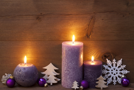 Christmas Decoration With Light Purple Candles, Christmas Tree, Christmas Ball, Snowflake, Fir Cone. Peaceful Atmosphere With Candlelight. Brown Wooden Background For Copy Space. Vintage Rustic Style Stock Photo