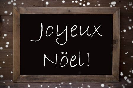 joyeux: Brown Blackboard With French Text Joyeux Noel Means Merry Christmas As Greeting Card. Wooden Background. Vintage Rustic Style. Snowflakes Symbolizing Christmas Or Winter Season. Stock Photo