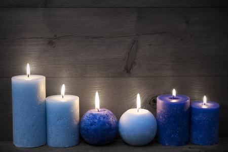 luz de vela: Decoración de Navidad con azul claro y oscuro velas. Pacífica, ambiente romántico con velas. Fondo de madera por espacio de copia. Estilo rústico de la vendimia. Imagen blanco y negro con color Hotspots