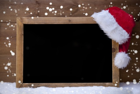 business christmas: Brown Christmas Blackboard With Copy Space, Free Text As Greeting Card. Red Christmas Decoration, Loop, Santa Hat, Snowflakes. Wooden Background With Snow. Vintage Rustic Style.