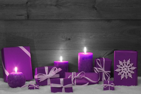 Christmas Decoration With Purple Candles, Handmade Christmas Gifts, Presents,Snowflake, Snow. Peaceful Atmosphere With Candlelight. Wooden,Vintage,Rustic Background.Copy Space. Black And White Image