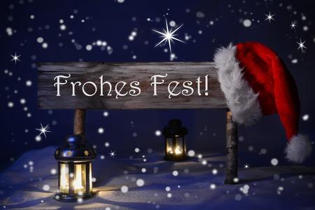 landschap: Houten Kerstmis Teken En Santahoed Met Sneeuw. Duitse tekst Fohes Fest Middelen Vrolijke Kerstmis voor de Groeten van Seizoenen. Blue Silent Night Met Sneeuwvlokken en fonkelende sterren. Lantaarn en Candlelight