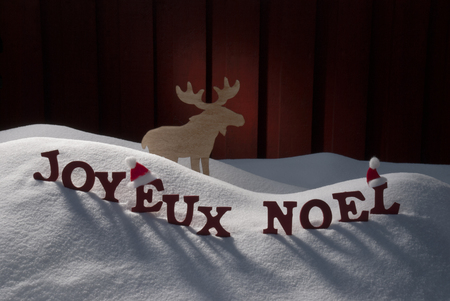 santa moose: Red Letters Building French Word Joyeux Noel Means Merry Christmas.Decoration Card For Seasons Greetings. Snow And Snowy Scenery With Moose And Santa Hat. Wooden Background. Christmas Atmosphere Stock Photo