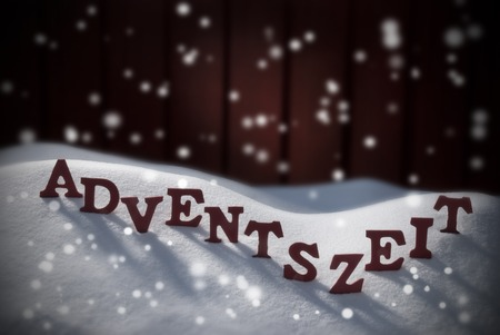 christmas atmosphere: Wooden Letters Building Red German Word Adventszeit Means Christmas Time Or Christmas Season. Snow And Snowy Scenery In Front Of Red Wooden Background. Christmas Atmosphere Stock Photo
