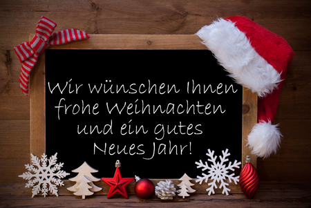 Blackboard With Red Santa Hat And Christmas Decoration like Snowflake, Tree, Christmas Ball, Fir Cone, Star. German Text Danke Means Thank You. Brown Wooden Background Standard-Bild