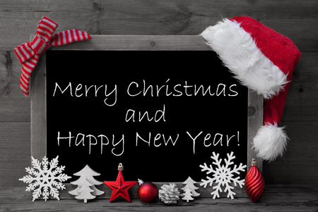 like english: Black And White Blackboard With Red Santa Hat And Christmas Decoration like Snowflake, Tree, Christmas Ball, Fir Cone, Star. English Text Merry Christmas And Happy New Year. Wooden Background