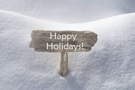christmas atmosphere: Wooden Christmas Sign With Snow In Snowy Scenery. English Text Happy Holidays For Seasons Greetings Or Christmas Greetings. Christmas Atmosphere.