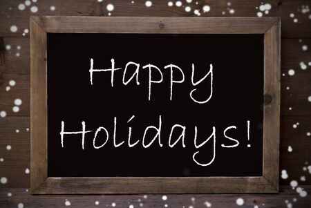 greeting season: Brown Blackboard With English Text Happy Holidays As Greeting Card. Wooden Background. Vintage Rustic Style. Snowflakes Symbolizing Christmas Or Winter Season.