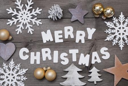 Weißer Schrift mit Word-frohe Weihnachten auf braune hölzerne Hintergrund. Weihnachtsgruß-Karte. Grau Rustikal, Vintage-Stil. Weihnachtsdekoration, Weihnachtsbaum, Schneeflocken, Goldene Weihnachtskugel