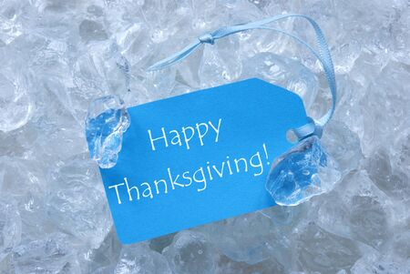 icecubes: Light Blue Label With Ribbon On White Transparent Curshed Ice Cubes As Background. English Text Happy Thanksgiving For Cool Greetings.Close Up Or Macro View. Stock Photo