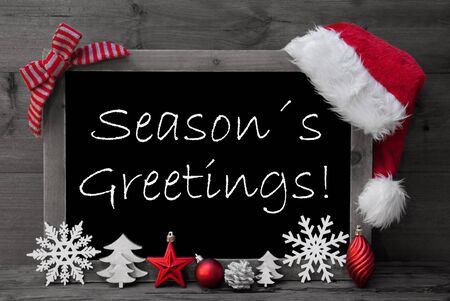 like english: Black And White Blackboard With Red Santa Hat And Christmas Decoration like Snowflake, Tree, Christmas Ball, Fir Cone, Star. English Text Seasons Greetings. Wooden Background Stock Photo