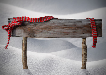 Brown Wooden Christmas Sign On White Snow. Snowy Scenery. Red Ribbon, Copy Space For Advertisement. Christmas Decoration Or Christmas Card. Rustic Or Vintage Syle. Standard-Bild