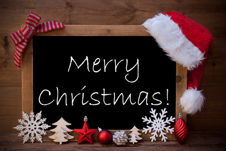 like english: Blackboard With Red Santa Hat And Christmas Decoration like Snowflake, Tree, Christmas Ball, Fir Cone, Star. English Text Merry Christmas. Brown Wooden Background