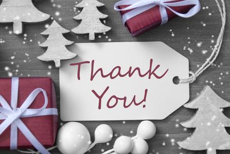 Schwarz und Weiß-Nahaufnahme von Etikett mit Band, Rot Geschenk, Geschenk, Band und Baum mit Schneeflocken. Weihnachtsdekoration oder eine Karte auf Holzuntergrund. Englisch Text Danke