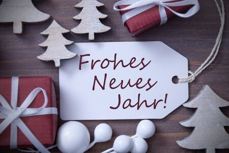 jahr: Black and White Close Up Of Label With Ribbon,Red Gift,Present, Ribbon And Tree. Christmas Decoration Or Card On Wooden Background. German Text Frohes Neues Jahr Means Happy New Year