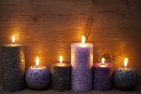 candlelight: Christmas Decoration With Light Purple, Lavender And Black Candles. Peaceful, Romantic Atmosphere With Candlelight. Wooden Background For Copy Space. Vintage Rustic Style