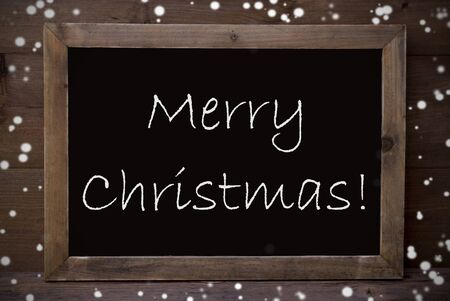 greeting season: Brown Blackboard With English Text Merry Christmas As Greeting Card. Wooden Background. Vintage Rustic Style. Snowflakes Symbolizing Christmas Or Winter Season.