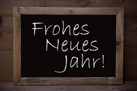 neues: Brown Blackboard With German Text Frohes Neues Jahr Means Happy New Year As Christmas Greeting Card. Wooden Background. Vintage Rustic Style. Stock Photo