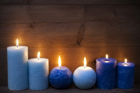 candlelight: Christmas Decoration With Light And Dark Blue Candles. Peaceful, Romantic Atmosphere With Candlelight. Brown Wooden Background For Copy Space. Vintage Rustic Style