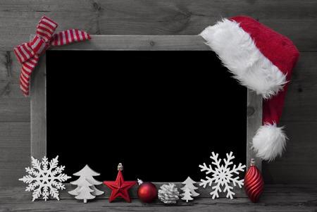 Schwarzweiß-Weihnachts Tafel mit Kopie Raum, Freitext. Red Weihnachtsdekoration, Schleife, Weihnachtsmütze, Weihnachtskugel, Weihnachtsbaum, Schneeflocke. Hölzernen Hintergrund. Weinlese rustikalen Stil.