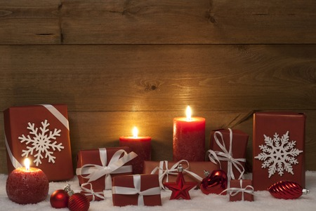 Christmas Decoration With Red Candles, Handmade Christmas Gifts,Presents,Christmas Ball,Snowflake,Snow. Peaceful Atmosphere With Candlelight.Gift Giving. Wooden Background.Copy Space. Vintage Rustic