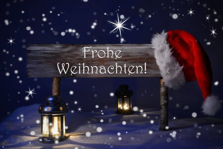 weihnachten: Wooden Christmas Sign And Santa Hat With Snow. German Text Fohe Weihnachten Means Merry Christmas For Seasons Greetings. Blue Silent Night With Snowflakes And Sparkling Stars. Lantern And Candlelight Stock Photo