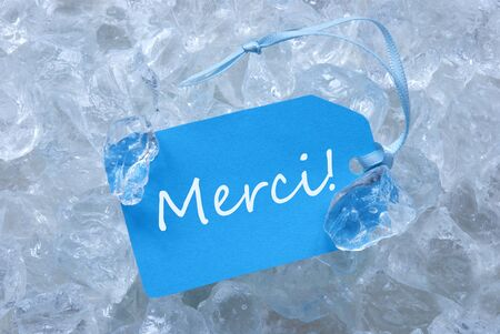 merci: Light Blue Label With Ribbon On White Transparent Curshed Ice Cubes As Background. French Text Merci Means Thank You For Cool Greetings.Close Up Or Macro View. Stock Photo