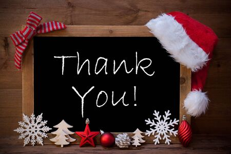 like english: Blackboard With Red Santa Hat And Christmas Decoration like Snowflake, Tree, Christmas Ball, Fir Cone, Star. English Text Thank You. Brown Wooden Background