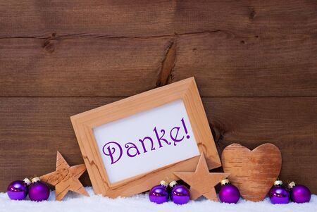 christmas tree ball: Brown Christmas Card With Purple Christmas Decoration On White Snow. Picture Frame With German Text Danke Means Thank You, Star, Heart And Christmas Tree Ball. Rustic Wooden Background