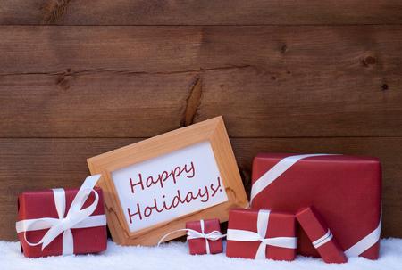 Red Christmas Decoration Op Sneeuw, Christmas Gifts, presenteert. Picture Frame Met Engels tekst Happy Holidays. Rustieke, Vintage bruine houten achtergrond. Feestelijke sneeuw Kerstkaart Stockfoto