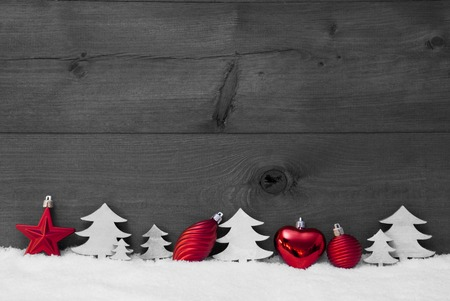 Festive Christmas Decoration On White Snow. Christmas Ball, Christmas Tree, Star. Rustic, Vintage Wooden Background. Copy Space For Advertisement. Black And White Image With Red Color Hotspot