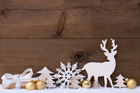 wooden reindeer: Christmas Card With Golden Festive Decoration On Snow. Gift, Present, White Reindeer, Christmas Ball, Christmas Tree,, Snowflake. Brown, Rustic, Vintage Wooden Background. Copy Space For Advertisement