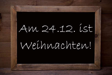 weihnachten: Brown Blackboard With German Text Am 24.12 Ist Weihnachten Means Merry Christmas As Greeting Card. Wooden Background. Vintage Rustic Style. Stock Photo