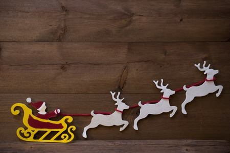 santa moose: Christmas Decoration, Red Santa Claus, Yellow Sled And White Reindeer. Brown Vintage Wooden Background With Copy Space. Christmas Card For Seasons Greetings
