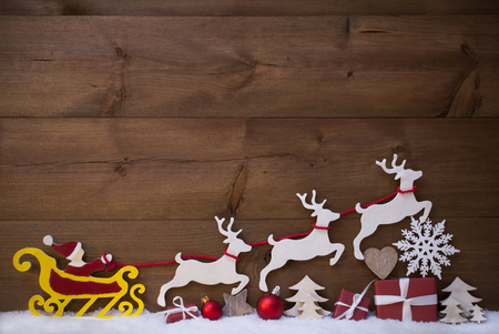 Christmas Decoration With Red Santa Claus, Yellow Sled, Reindeer On White Snow. Gift, Present, Christmas Tree, Ball, Snowflakes, Heart. Brown, Rustic, Vintage Wooden Background With Copy Space Standard-Bild