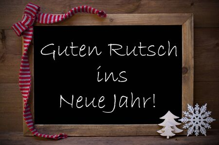ins: Brown Christmas Blackboard With German Text Guten Rutsch Ins Neue Jahr Means Happy New Year. Christmas Decoration, Christmas Tree, Snowflake Red Loop. Wooden Background. Vintage Rustic Style. Stock Photo