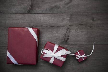 wraps: Tres Regalos Rojo Gris de Navidad, regalos con la cinta blanca como decoración. Shabby Chic, Rústico, Fondo de madera de la vendimia. Espacio en blanco para el anuncio. Tarjeta Para Saludos del cumpleaños. En blanco y negro
