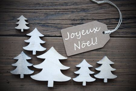 french text: Brown Christmas Label With Ribbon On Wooden  Background With White Christmas Trees. Vintage Style. Label With French  Text Joyeux Noel Means Merry Christmas For Christmas Or Season Greetings Stock Photo