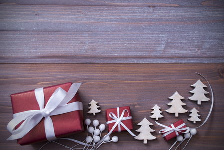 wood trade: Red Christmas Gifts, Presents, White Ribbon With Christmas Trees As Decoration. Shabby Chic, Rustic, Vintage Wooden Background. Copy Space For Advertisement. Card For Birthday Greetings