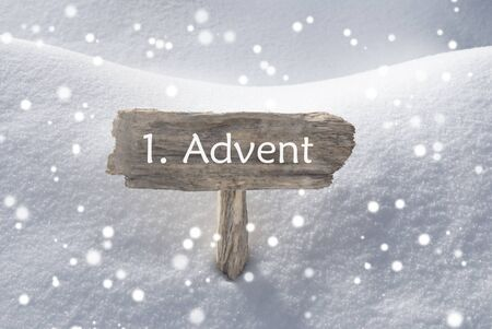 christmas atmosphere: Wooden Christmas Sign With Snow In Snowy Scenery. German Text 1 Advent Means Christmas Time For Seasons Greetings Or Christmas Greetings. Christmas Atmosphere With Snowflakes