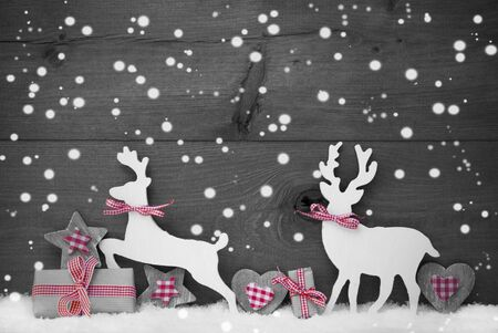 wooden reindeer: Christmas Decoration With Reindeer Couple In Love On White Snow, Snowflakes. Christmas Gift, Present, Ribbon, Heart, Star. Gray, Rustic, Vintage Wooden Background. Black And White Image. Red Hotspot
