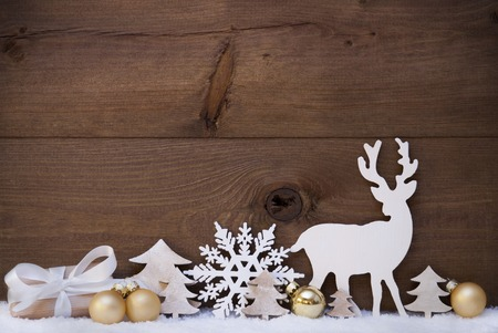 Christmas Card With Golden Festive Decoration On Snow. Gift, Present, White Reindeer, Christmas Tree, Christmas Ball, Snowflake. Brown, Rustic, Vintage Wooden Background. Copy Space For Advertisement Standard-Bild