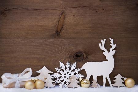 Weihnachtskarte mit goldenen festliche Dekoration auf Schnee. Geschenk, Geschenk, Weiß Rentier, Weihnachtsbaum, Weihnachtsball, Schneeflocke. Brown, Rustikal, Weinlese-Holz-Hintergrund. Kopieren Sie Platz für Werbung
